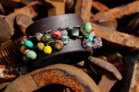 charm bracelet on a leather cuff